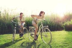 Pares felices que tienen una raza de bicicletas en la naturaleza Imagen de archivo libre de regalías