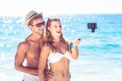 Pares felices que toman el selfie con el palillo del selfie imágenes de archivo libres de regalías