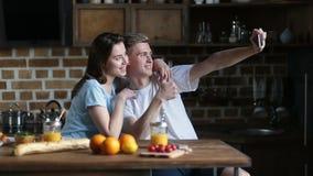 Pares felices que toman el selfie con el teléfono en cocina almacen de metraje de vídeo