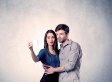 Pares felices que toman el selfie con la pared clara Foto de archivo libre de regalías