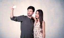 Pares felices que toman el selfie con la pared clara Fotografía de archivo