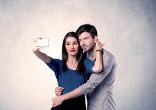 Pares felices que toman el selfie con la pared clara Fotografía de archivo libre de regalías