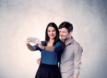 Pares felices que toman el selfie con la pared clara Imagenes de archivo