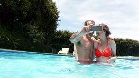 Pares felices que toman el selfie del teléfono móvil en piscina metrajes