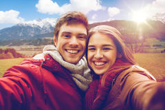 Pares felices que toman el selfie sobre las montañas de las montañas Imágenes de archivo libres de regalías