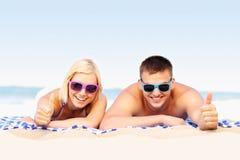 Pares felices que toman el sol en la playa Fotos de archivo