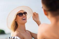 Pares felices que toman el sol en la playa del verano Imagen de archivo libre de regalías