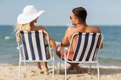 Pares felices que toman el sol en sillas en la playa del verano Imagenes de archivo