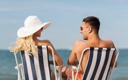 Pares felices que toman el sol en sillas en la playa del verano Imágenes de archivo libres de regalías
