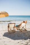 Pares felices que toman el sol en sus sillas de cubierta Foto de archivo