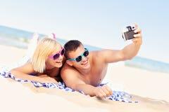 Pares felices que toman imágenes en la playa imagen de archivo libre de regalías