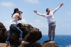 Pares felices que toman la foto en un acantilado en Hawaii Foto de archivo libre de regalías