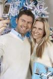 Pares felices que toman la imagen con el teléfono celular en Front Of Christmas Tree Fotografía de archivo libre de regalías