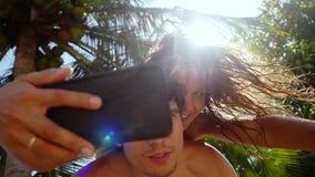 Pares felices que toman las fotos del selfie en smartphone debajo de las palmeras y del sol en el fondo La mujer cuelga en showld almacen de metraje de vídeo