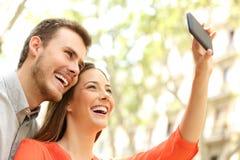 Pares felices que toman selfies en la calle Foto de archivo