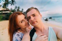 Pares felices que toman una foto en una playa imágenes de archivo libres de regalías