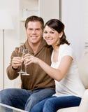 Pares felices que tuestan con champán Foto de archivo libre de regalías