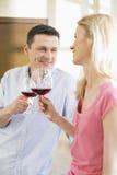 Pares felices que tuestan las copas de vino rojas en cocina Imagen de archivo libre de regalías