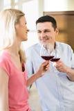 Pares felices que tuestan las copas de vino rojas en cocina Foto de archivo libre de regalías