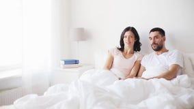 Pares felices que ven la TV en cama en casa almacen de metraje de vídeo