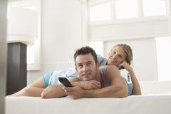 Pares felices que ven la TV en casa Foto de archivo libre de regalías