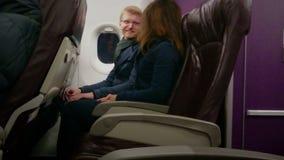 Pares felices que viajan en avión el vacaciones, llevando a cabo las manos, disfrutando de vuelo almacen de metraje de vídeo