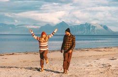 Pares felices que viajan junto paseo alegre en la playa fotografía de archivo
