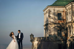 Pares felices sensuales que presentan y que abrazan cerca de castillo viejo en el sunse Imagen de archivo libre de regalías