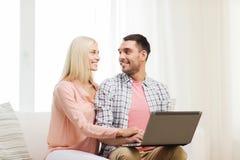 Pares felices sonrientes con el ordenador portátil en casa Imagenes de archivo