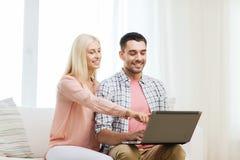 Pares felices sonrientes con el ordenador portátil en casa Imagen de archivo