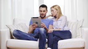 Pares felices sonrientes con PC de la tableta en casa almacen de metraje de vídeo