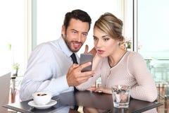 Pares felices sorprendidos que miran el smartphone la barra Foto de archivo libre de regalías