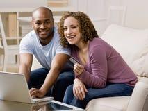Pares felices usando de la tarjeta de crédito a hacer compras en línea Imágenes de archivo libres de regalías