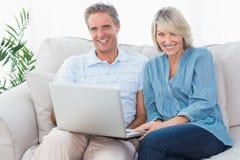 Pares felices usando el ordenador portátil junto en el sofá que mira el camer Fotos de archivo libres de regalías