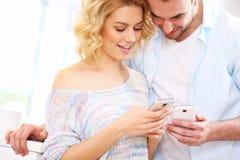 Pares felices usando el teléfono elegante en casa Fotos de archivo