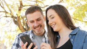 Pares felices usando el teléfono elegante en un parque