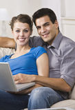 Pares felices usando la computadora portátil Fotografía de archivo libre de regalías