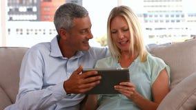 Pares felices usando la PC de la tableta junto almacen de metraje de vídeo