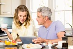 Pares felices usando la tableta y el desayuno el tener Foto de archivo libre de regalías