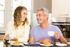Pares felices usando la tableta y el desayuno el tener Foto de archivo