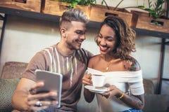 Pares felices usando las tabletas digitales mientras que se sienta en café Imagen de archivo