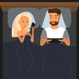 Pares felices usando los dispositivos digitales en cama en la noche