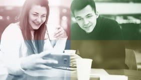 Pares felices usando smartphone junto y café de consumición en café Fotografía de archivo libre de regalías