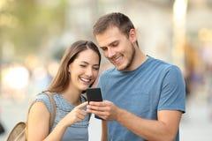 Pares felices usando un teléfono elegante en la calle Foto de archivo libre de regalías