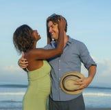 Pares felices y rom?nticos de la raza mixta con la mujer afroamericana negra atractiva y el hombre blanco que juegan en la playa  imagenes de archivo