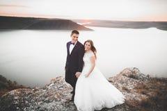 Pares felizes à moda elegantes do casamento, noiva, noivo lindo no fundo do mar e céu Imagens de Stock