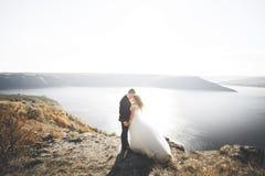 Pares felizes à moda elegantes do casamento, noiva, noivo lindo no fundo do mar e céu Fotografia de Stock Royalty Free