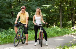 Pares felizes atrativos no bicicletas em um campo Imagem de Stock