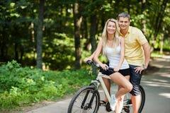 Pares felizes atrativos no bicicletas em um campo Fotografia de Stock Royalty Free