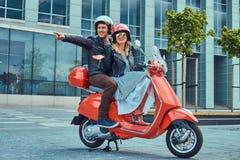 Pares felizes atrativos, um homem considerável e montada fêmea 'sexy' junto em um 'trotinette' retro vermelho em uma cidade foto de stock royalty free